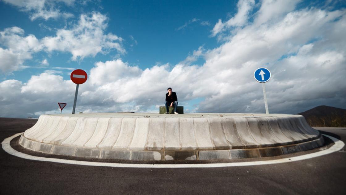 Ein Mann sitzt auf einer Verkehrsinsel und denkt nach