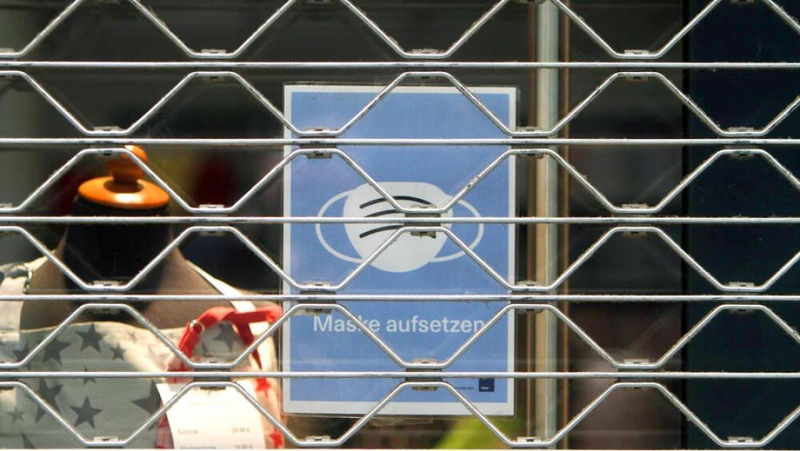 Schild mit Piktogramm Maskenpflicht im Schaufenster eines mit Rolltor verschlossenen Geschäfts in der Innenstadt von Köln, Nordrhein Westfalen, Deutschland (imago images / Ralph Peters)