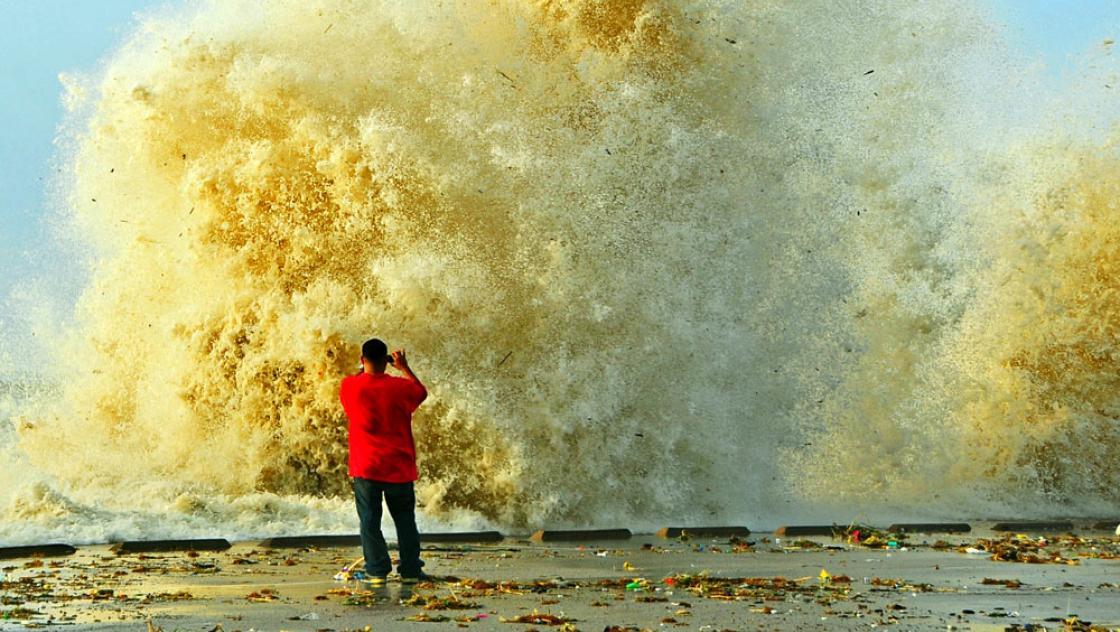 Ein Mann fotografiert eine Welle, die sich an einer Kaimauer bricht